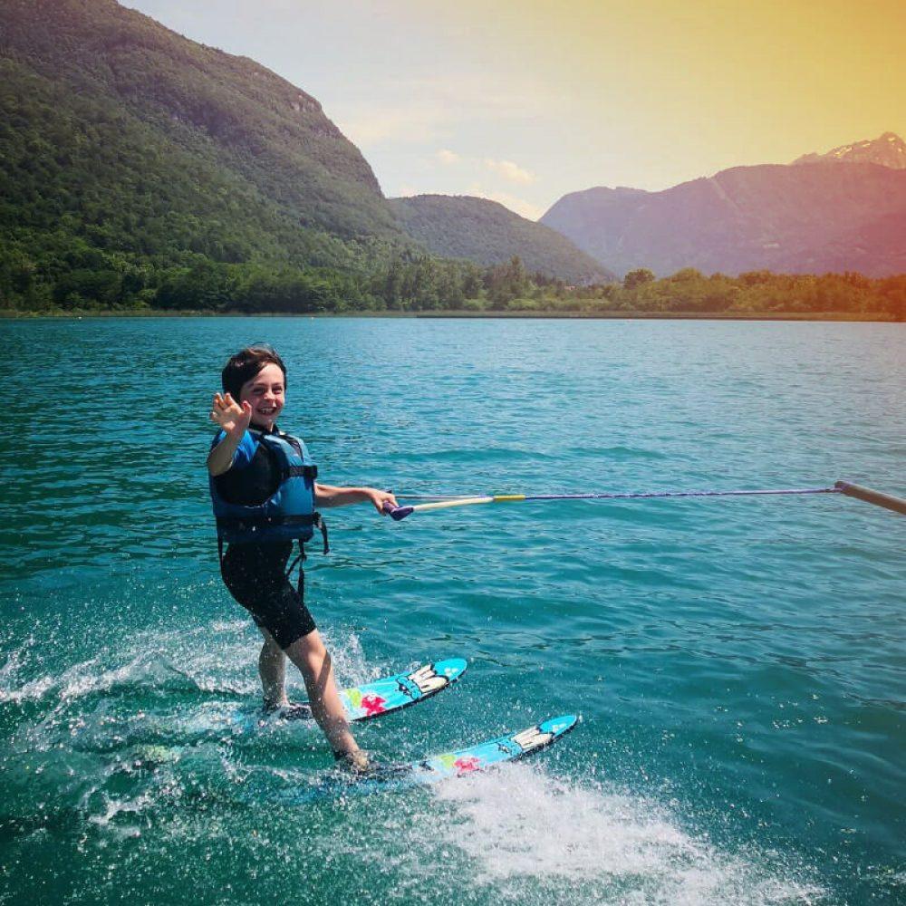 Garçon sur des skis nautiques sur le lac d'Annecy